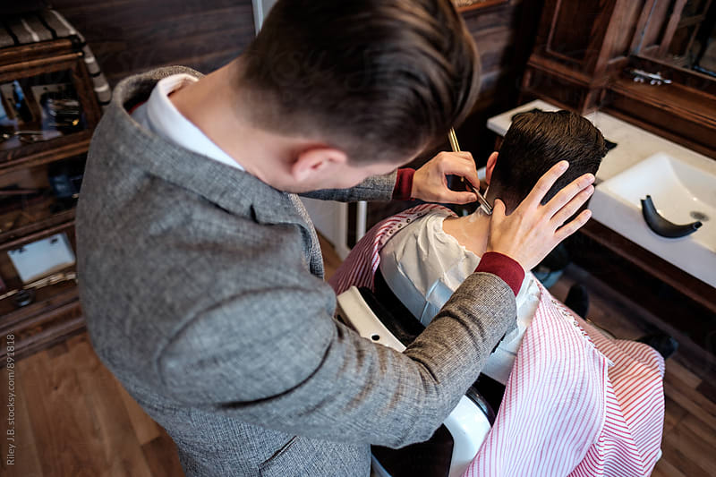 Looking down in the neck of a client being shaved with a straight razor by a gentleman barber. by Riley J.B. for Stocksy United