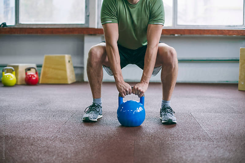 Man Lifting a Kettle Bell by Lumina for Stocksy United