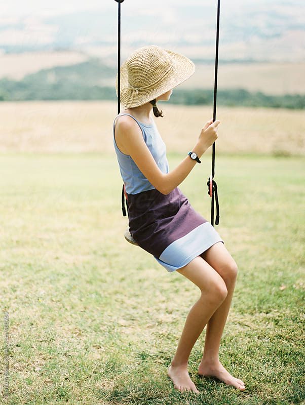 Girl sitting on a swing by Kirstin Mckee for Stocksy United