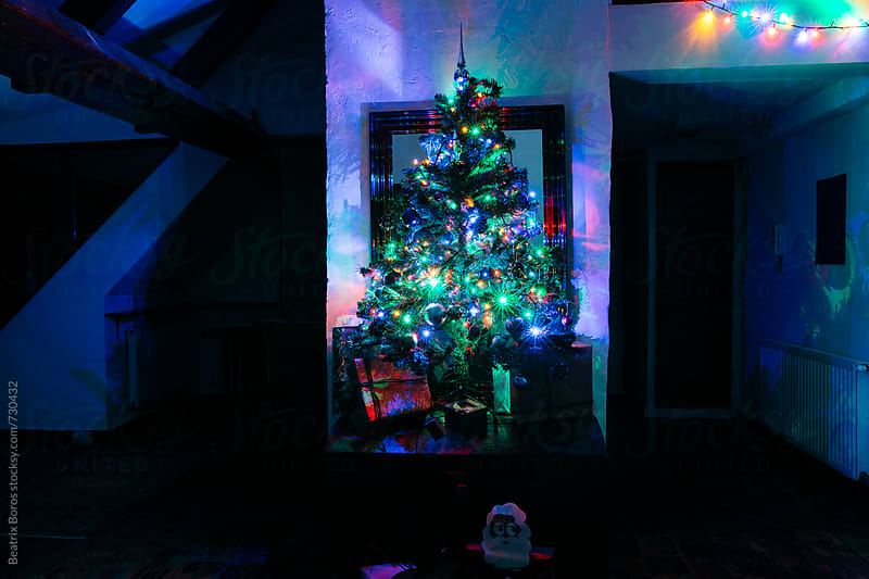 Christmas tree and decor i front of a wall by Beatrix Boros for Stocksy United