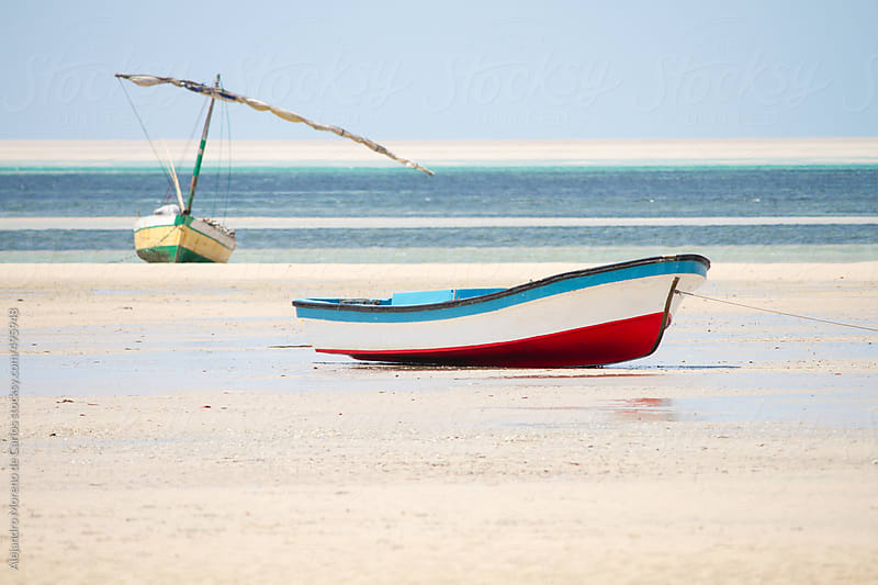 Boats on the sand of a lonely beach. Vilanculos, Mozambique by Alejandro Moreno de Carlos for Stocksy United