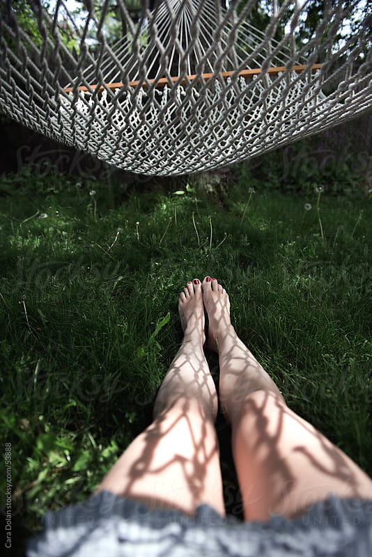 Woman lies on the grass under a hammock by Cara Dolan for Stocksy United