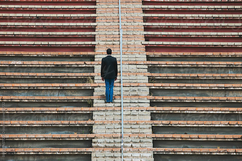Young businesman standing on street stairs. by BONNINSTUDIO for Stocksy United