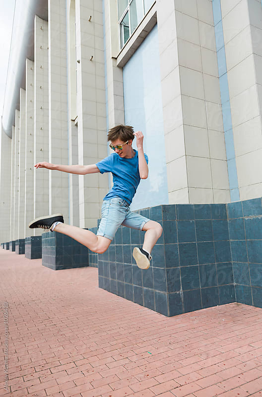 Happy young man jumping on the street  by Alexey Kuzma for Stocksy United
