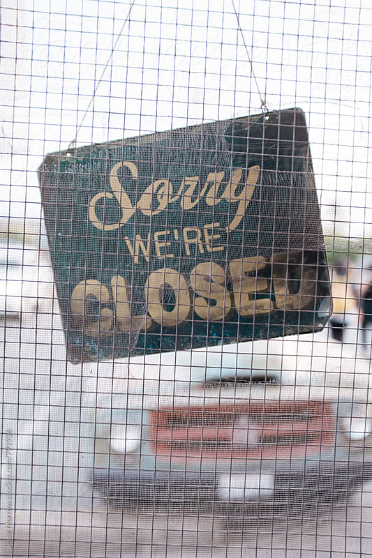 sorry we're closed vintage sign hanging in screen door by Jesse Morrow for Stocksy United