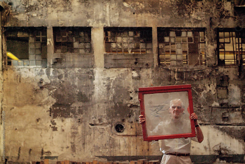 old man holding red frame in rural ambient by Marija Anicic for Stocksy United