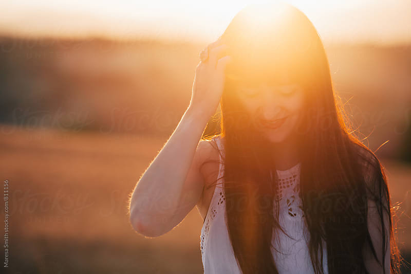 Brunette woman smiling and looking down with her hand in her hair at golden hour by Maresa Smith for Stocksy United