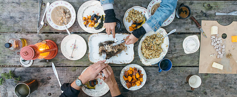 Full Thanksgiving dinner spread outside on picnic table by Jeremy Pawlowski for Stocksy United