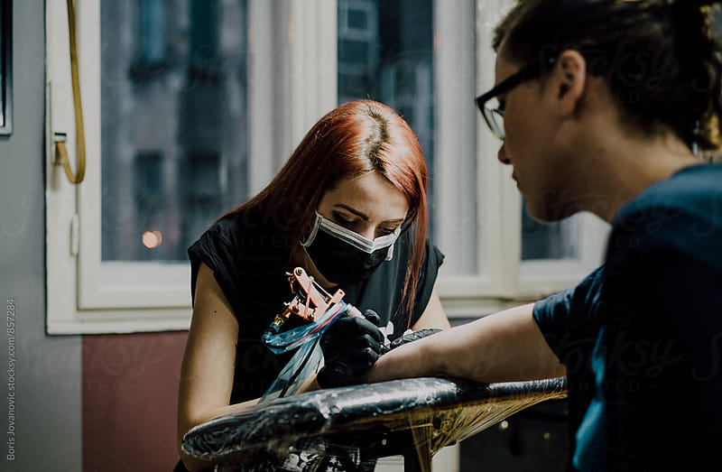 Tattoo artists doing a tattoo  by Boris Jovanovic for Stocksy United