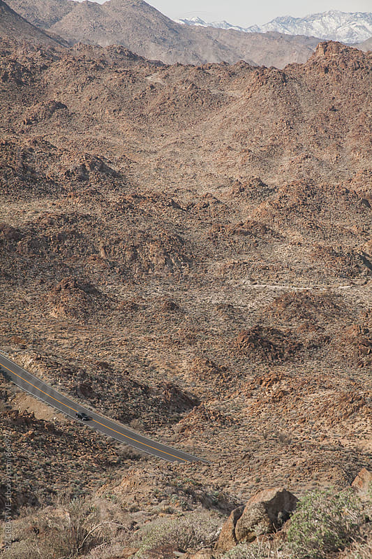 Looking down at a twisty muontain road descending to the desert. by Robert Zaleski for Stocksy United