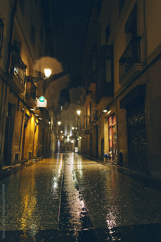 Empty shopping street on a rainy dark evening.  by Denni Van Huis for Stocksy United