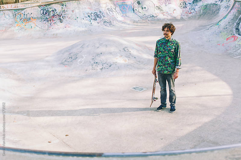 Young stylish man holding skateboard in a skatepark. by Denni Van Huis for Stocksy United