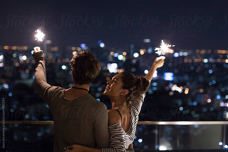 Young couple holding sparklers and looking at the city by Jovo Jovanovic for Stocksy United
