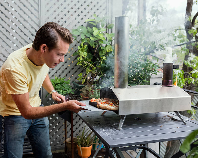 Man Cooking Pizza in Portable Wood Oven. by Jill Chen for Stocksy United