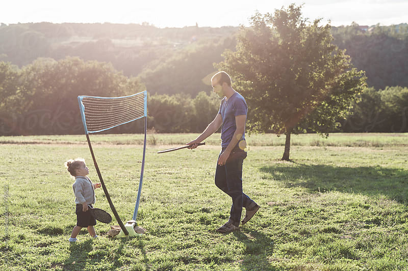 Father and toddler playing Racquetball at sunset by Lior + Lone for Stocksy United