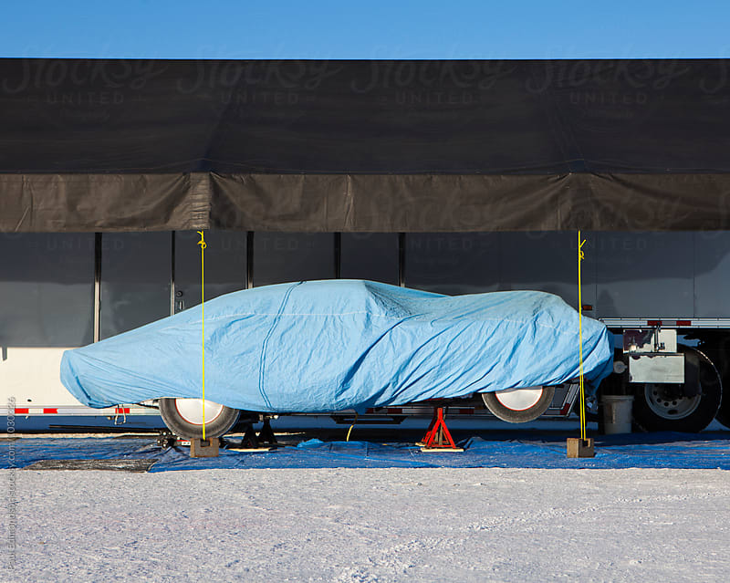Racing car covered in protective blue tarp, RV in background by Paul Edmondson for Stocksy United