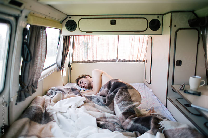 Young man sleeping in old camper van by Nabi Tang for Stocksy United