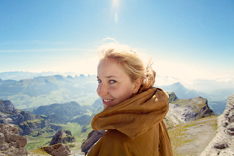 Happy woman on top of a mountains looking at the camera with the view behind her. by Denni Van Huis for Stocksy United