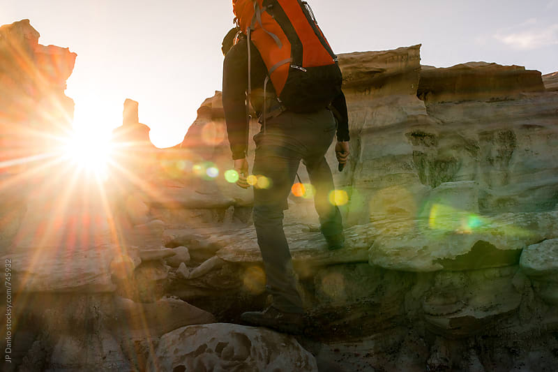 Backpacker Climbing Over Hoodoos in Bisti Badlands Wilderness Area New Mexico at Sunrise by JP Danko for Stocksy United