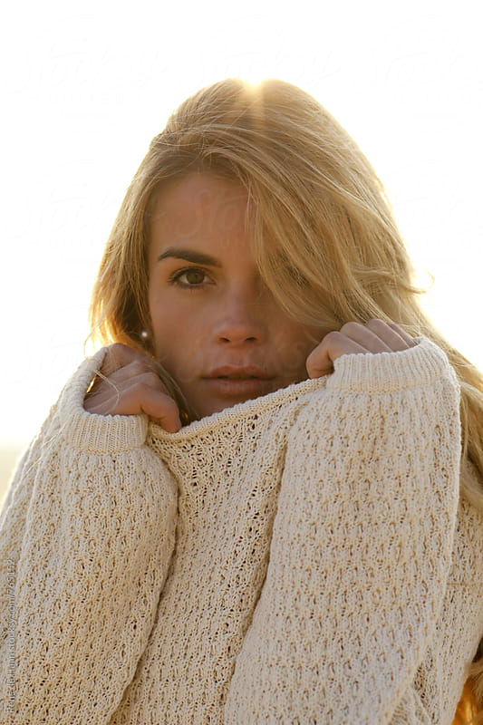 young blonde woman in white sweater at sunset by Rene de Haan for Stocksy United