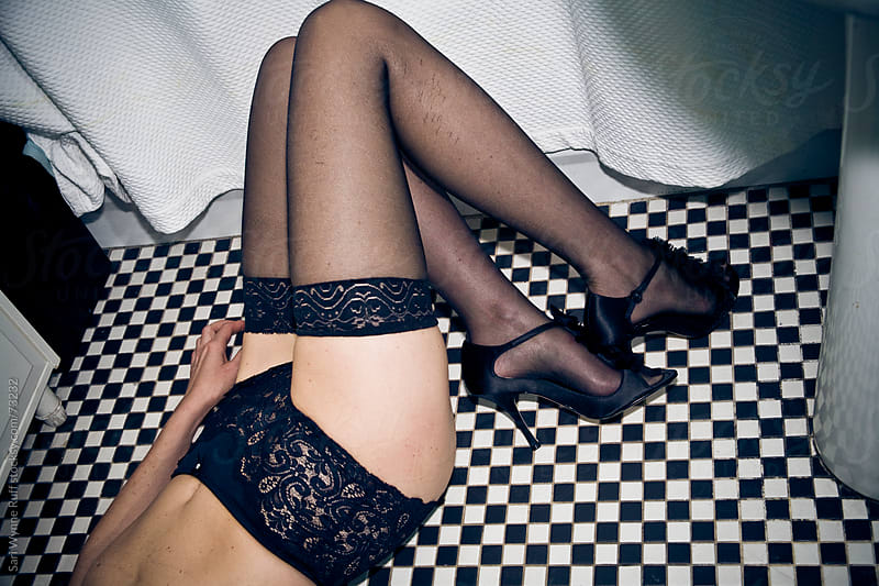 Woman's legs in thigh highs and heels bathroom floor by Sari Wynne Ruff for Stocksy United