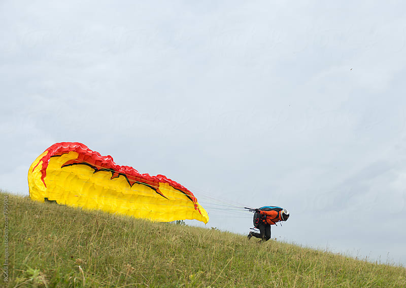 Paraglider running to rise his canopy and take flight by RG&B Images for Stocksy United