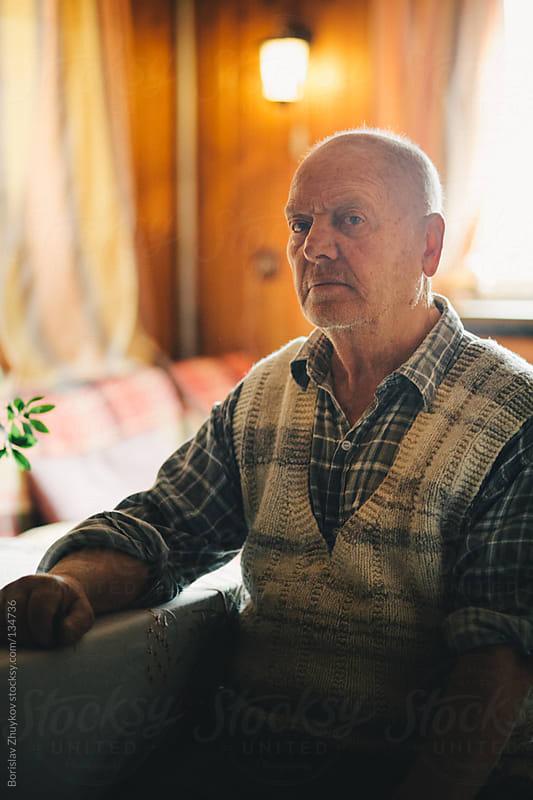 Portrait of an elderly man sitting on a chair looking ahead by Borislav Zhuykov for Stocksy United