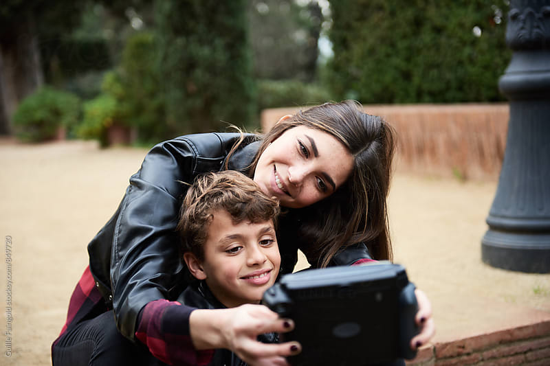 Older sister with her brother making selfie with instant camera by Guille Faingold for Stocksy United