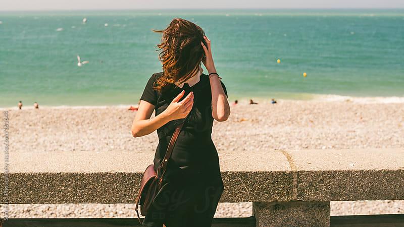 girl standing on windy boardwalk by Sam Hurd Photography for Stocksy United