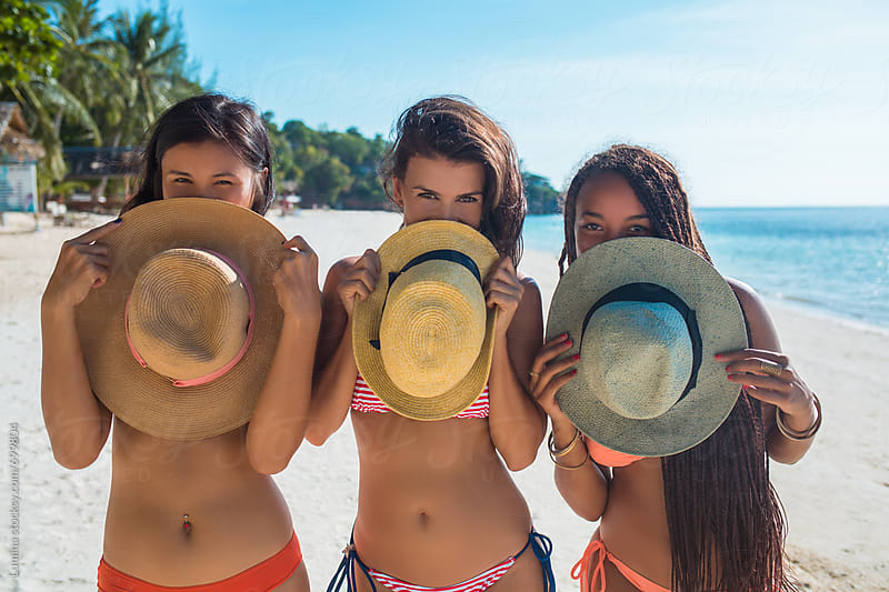 Girls in Bikinis Holding Hats by Lumina for Stocksy United