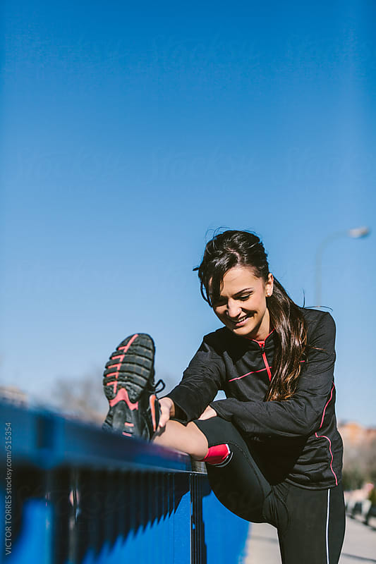 Runner Stretching in the Street by VICTOR TORRES for Stocksy United