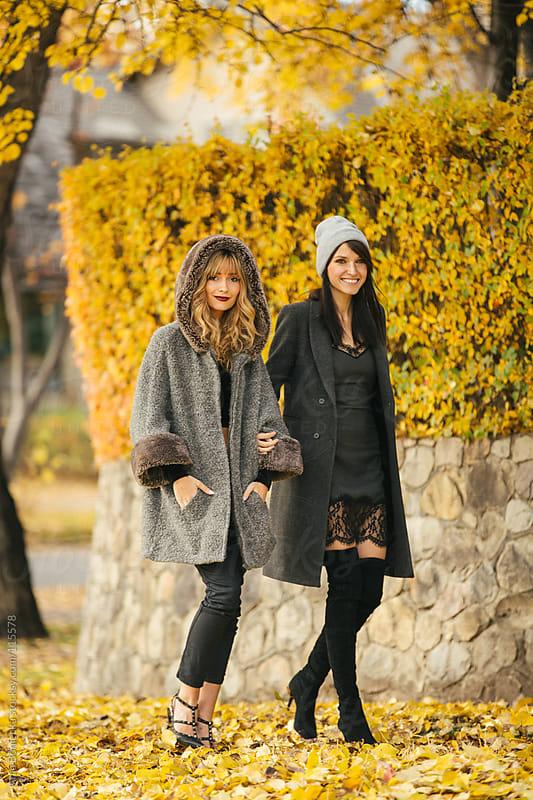 Two beautiful women walking side by side along the sidewalk in the fall smiling by Ania Boniecka for Stocksy United