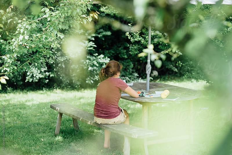 young woman writing in the shade in the garden by Léa Jones for Stocksy United