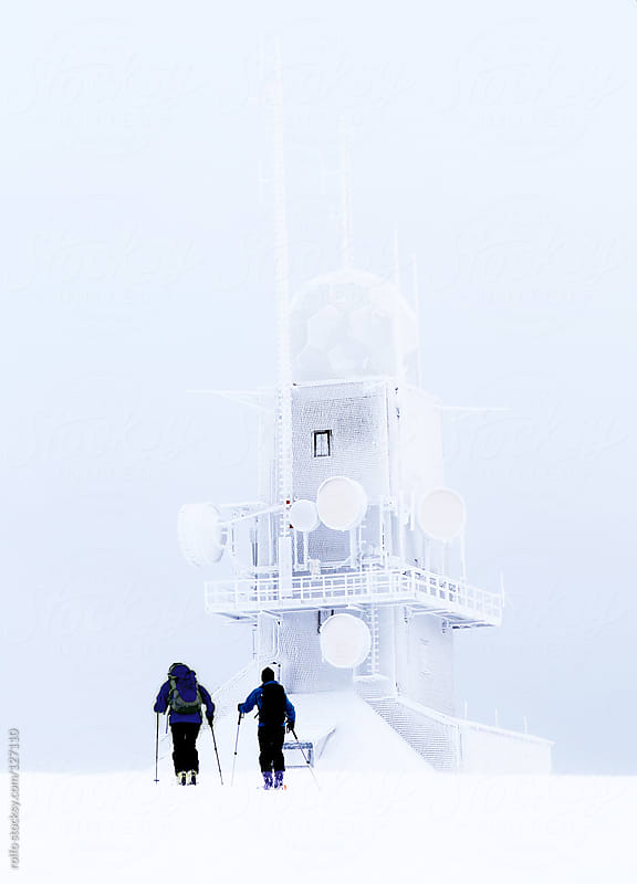 Cross-country skiers below a frozen tower by rolfo for Stocksy United