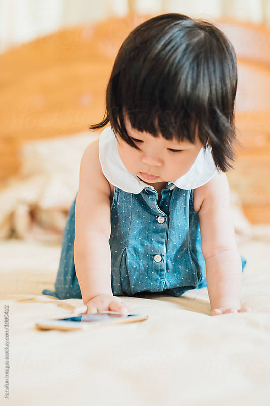 baby using cell phone by Pansfun Images for Stocksy United