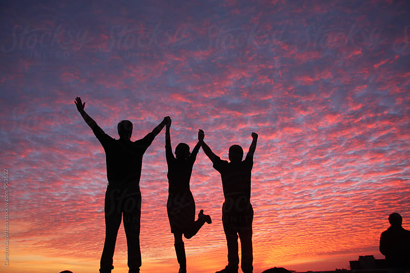 People with their arms raised in celebration with a vibrant, pink sky by Carolyn Lagattuta for Stocksy United