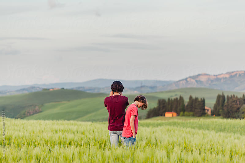Two boys standing in a field in Italy photographing the Tuscan landscapes by Cindy Prins for Stocksy United