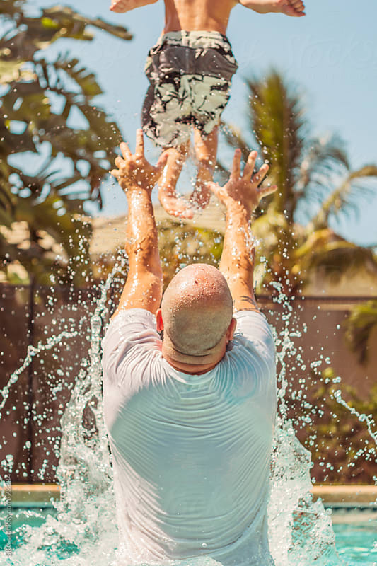 Father and Son Playing in the Pool by suzanne clements for Stocksy United