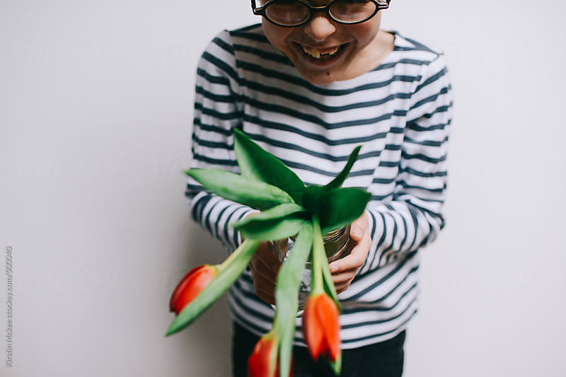 Boy giggling while holding a jar filled with tulips by Kirstin Mckee for Stocksy United