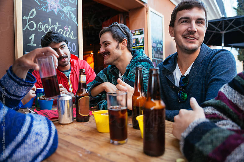 Group of young friends having drinks on a table at the outside of a touristic bar by Alejandro Moreno de Carlos for Stocksy United