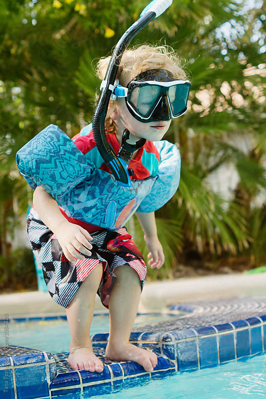 little boy wearing  snorkel  ready to jump into pool by Tana Teel for Stocksy United