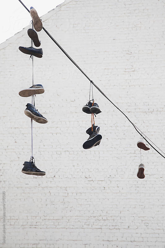 hanging shoes and white wall by Sonja Lekovic for Stocksy United