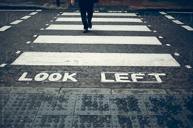 Look left written on the street with a man on a crosswalk  by Denni Van Huis for Stocksy United