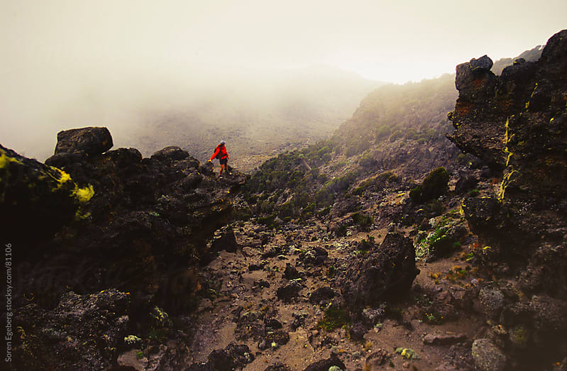 Climber in red jacket looking at view on volcanic rock on Mt. Kilimanjaro by Soren Egeberg for Stocksy United