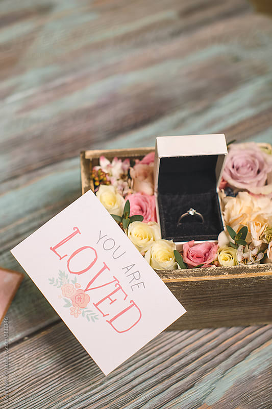 Close-up of ring in box with flowers and 'you are loved' card. by Danil Nevsky for Stocksy United