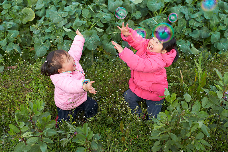 two happy little asian girls playing with soap bubble outdoor by cuiyan Liu for Stocksy United
