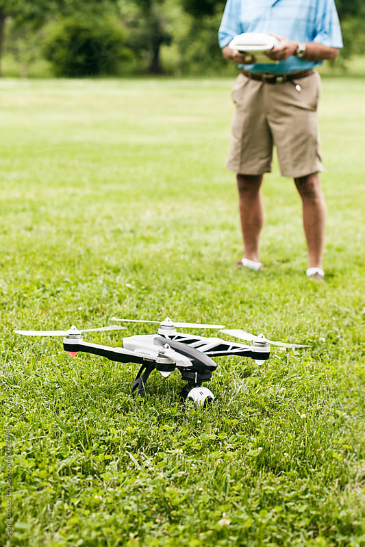 Drone Sits In Grass As Senior Male Prepares To Fly It by Sean Locke for Stocksy United