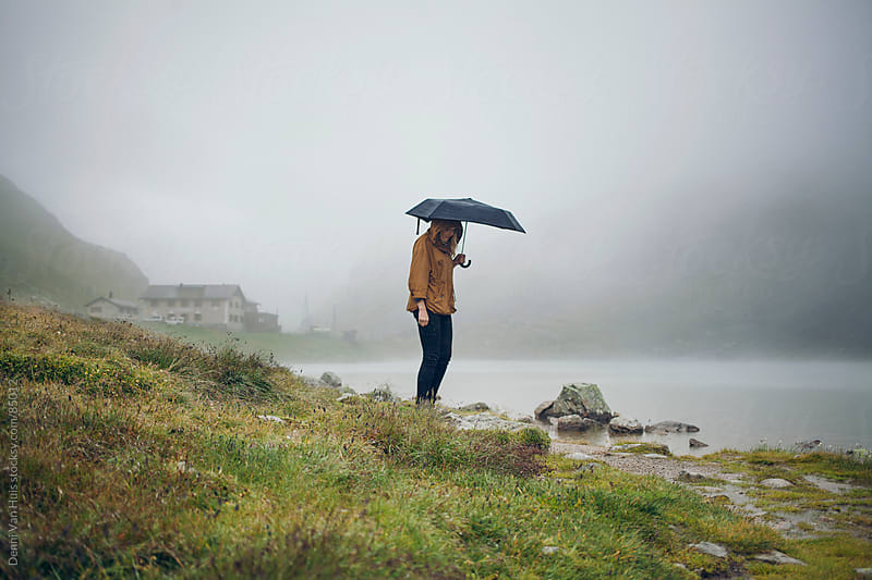 Woman holding an umbrella standing next to a mountain lake in the fog by Denni Van Huis for Stocksy United