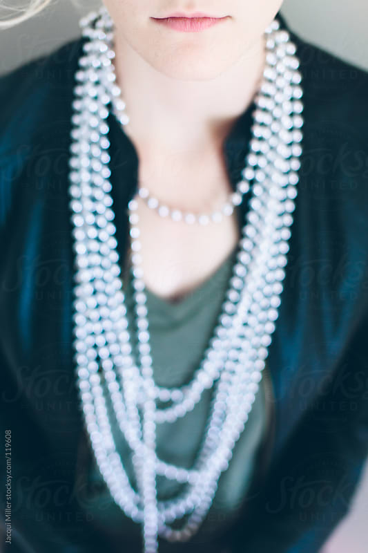 Girl wearing a long string of beads around her neck by Jacqui Miller for Stocksy United