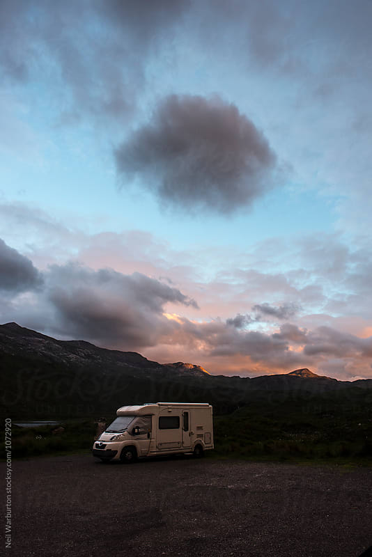 Camper van in the mountains at dusk by Neil Warburton for Stocksy United